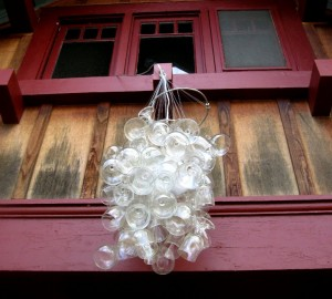 An outdoor chandelier made from wine glasses.